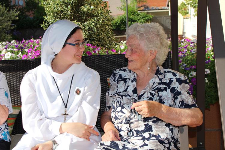 Hermana reparadora hablando con anciana en residencia