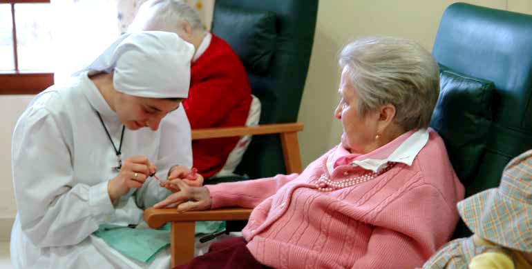 Hna. Lucía pintando las uñas a una abuelita